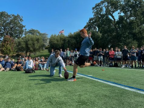 Senior Connor Williams kicks a football through the new field goal during assembly. The new schedule includes assembly twice a week.